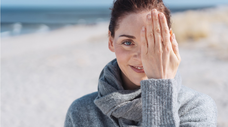 Tipps gegen raue Hände: Junge Frau hält sich die Hand vor eine Gesichtshälfte.