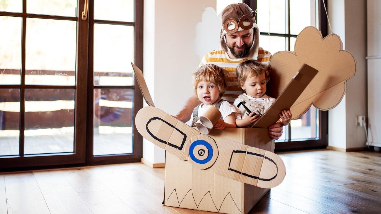 Lagerkoller: Zwei Kinder sitzen in einer zum Flugzeug umfunktionierten Kiste und werden vom Vater geschoben.