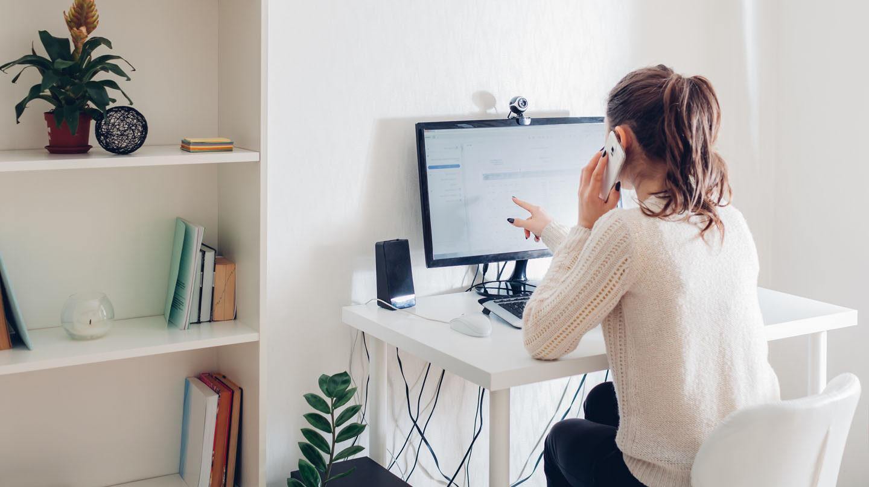 Thrombose im Bein: Junge Frau sitzt im Homeoffice am Schreibtisch vor dem Computer.