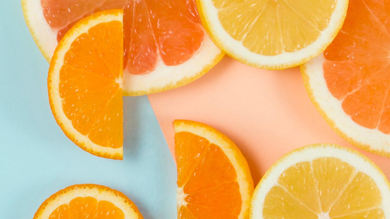 Mehr Glow für den Teint: Scheiben von Zitrusfrüchten auf hellblau-rosafarbenem Grund.