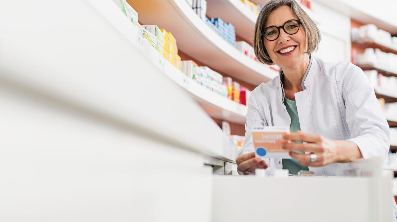 Arzneimittelsicherheit: Apothekerin vor Regal mit Medikamenten hält eine Medikamentenpackung in der Hand.