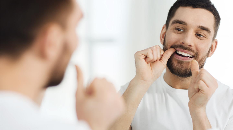 Zahnpflege: Junger Mann vor dem Spiegel putzt die Zahnzwischenräume mit Zahnseide.