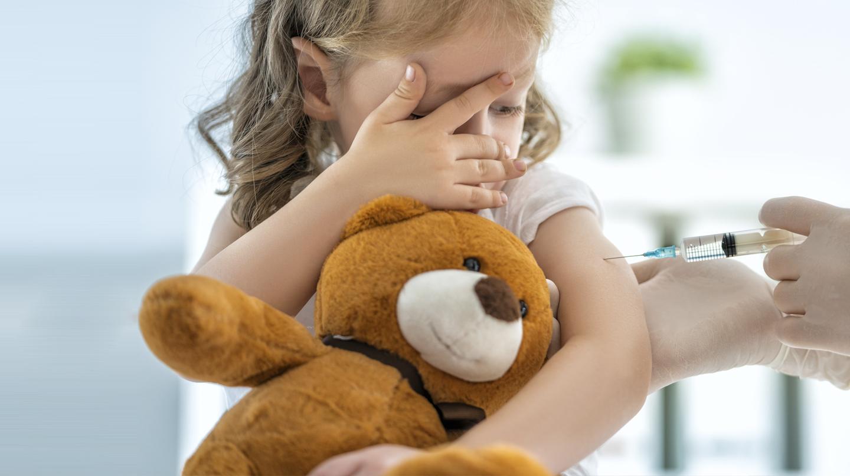 Angst vor Spritzen: Kleines Mädchen mit Teddybär im Arm schaut skeptisch auf die Spritze, die ihr der Arzt gerade verabreicht.